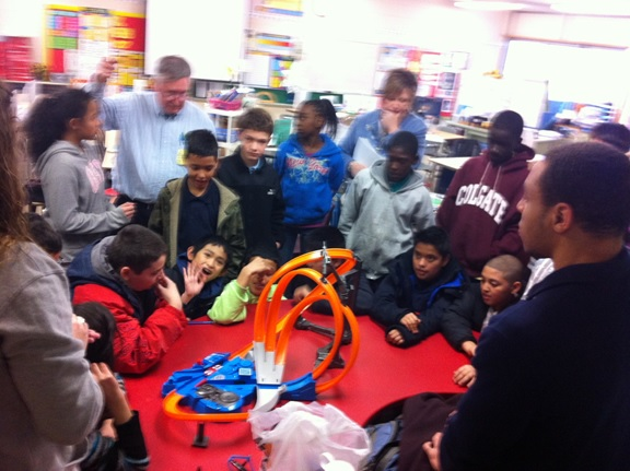 My teammates and me showing students a Hotwheels track.